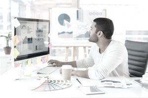 Small businessman looking at marketing graphs on a computer monitor in his home office.