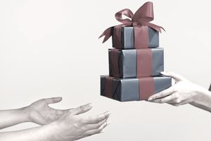 hands exchanging gifts with another person