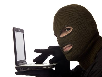 a man in a ski mask holding a laptop