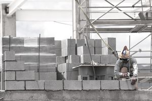 Bricklayer using a level and wearing safety clothing and harness building a cement or cinder block masonry infill wall on a multi-storey shopping centre, Cusco, Peru.