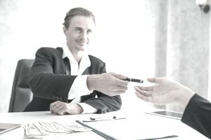business man handing pen to another business man contract on clipboard on desk with pile of cash next to it