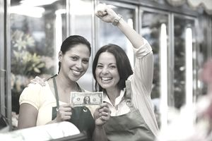 Two women business owners holding their first dollar after opening their business thanks to a loan.