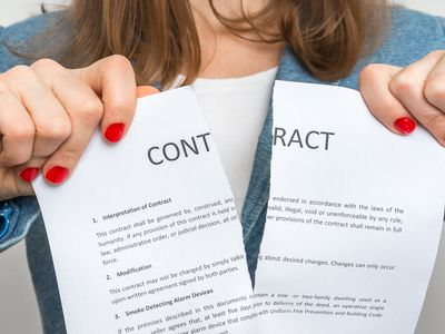 Woman ripping a contract in half to represent terminating a contract.