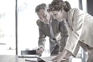 a pair of business people looking at documents together in an office