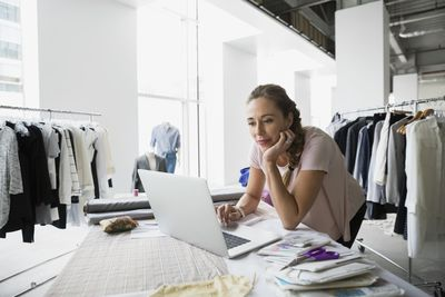 Woman business owner in her retail store on laptop