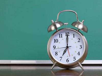 Close-Up Of Alarm Clock In Front Of Chalkboard