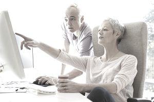 man and woman looking at home office computer