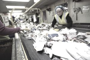 Workers on a Factory Assembly Line Sort Through Paper for Recycling