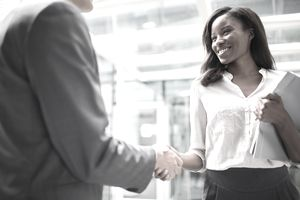 Businessman and businesswoman shaking hands in agreement