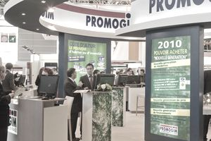 Large trade show display showing company name and attendees around several computers