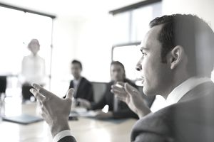 Closeup of businessman gesturing in conference room meeting