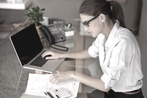 woman with laptop and calculator looking at paperwork