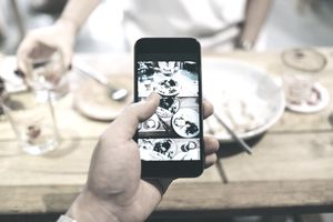 a person taking a photo of food with a smartphone
