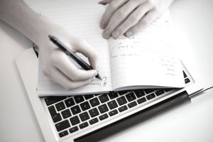 Close-up of human hand writing in notebook