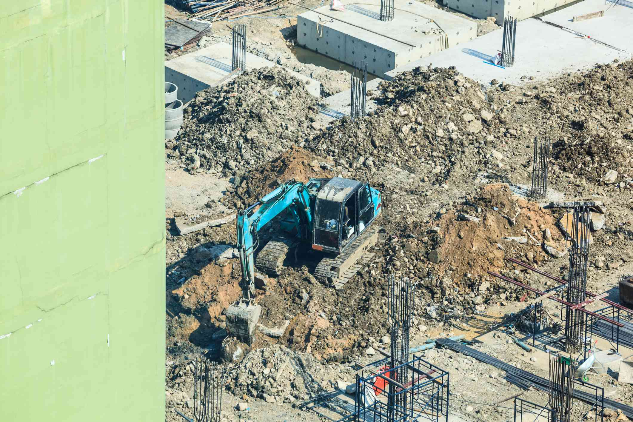 Construction Industry, Concrete building construction site. Concrete piles driven into the ground by excavator at foundation pit. Industrial Business, Working Place, Work and Labor, Economy concept.