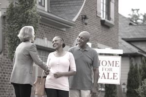 "Couple shaking woman's hand at house with ""for sale"" sign"