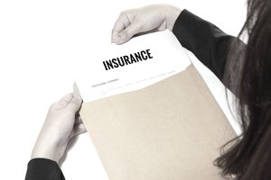 Cropped Hands Removing Insurance Document From Envelope At Table