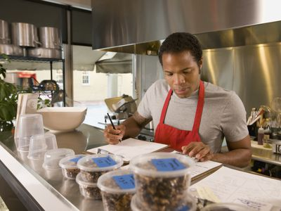 Cook with paperwork in commercial kitchen