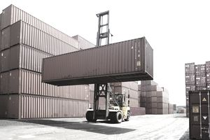 Forklift Raising a Freight Container into Storage