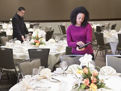 Event planner standing with tablet in ballroom with tables set up for a formal dinner event