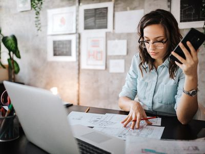 Young female entrepreneur using smart phone at modern working place