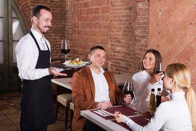 Male waiter carrying order for visitors