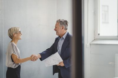 Realtor holding a real estate contract shaking hands with a buyer.