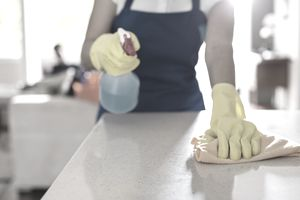 A woman wearing gloves and cleaning a counter