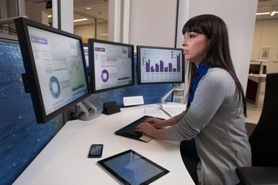 Financial analyst doing comparative market analysis on computers