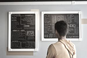 Man reading a restaurant menu written on chalkboards in a cafe.