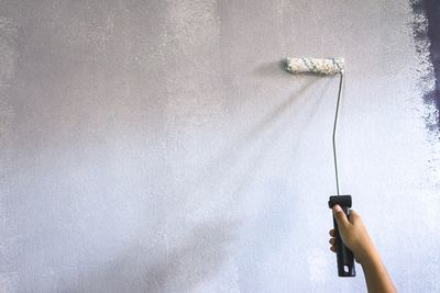Painting primer on a wall using a roller