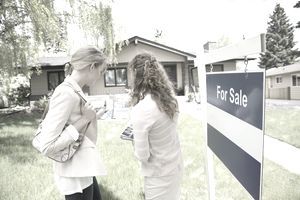 real estate agent and buyer standing in front of for sale sign