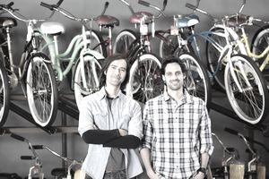 Bike shop owners standing in store.