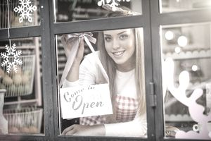 """Woman inside window of a small business hanging up the """"open"""" sign, representing the ease of opening a turnkey business."""