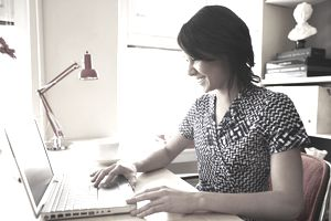 Young woman using laptop in creative office space, side view