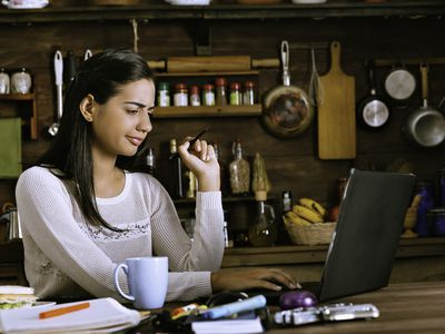 Worried or concern Hispanic young woman using laptop at the home office kitchen