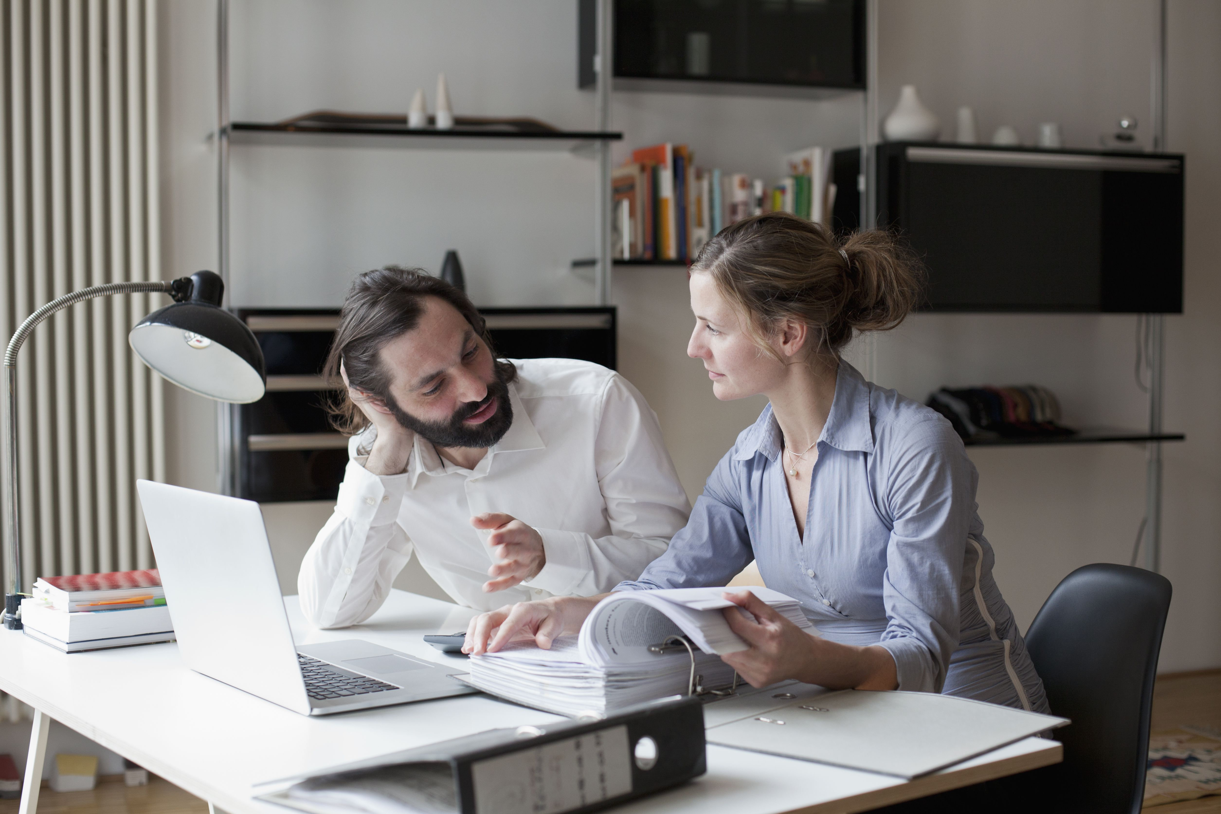 Mid adult couple discussing work at home