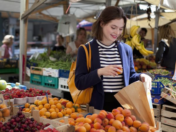 A woman shopping for fruit at a local outdoor market