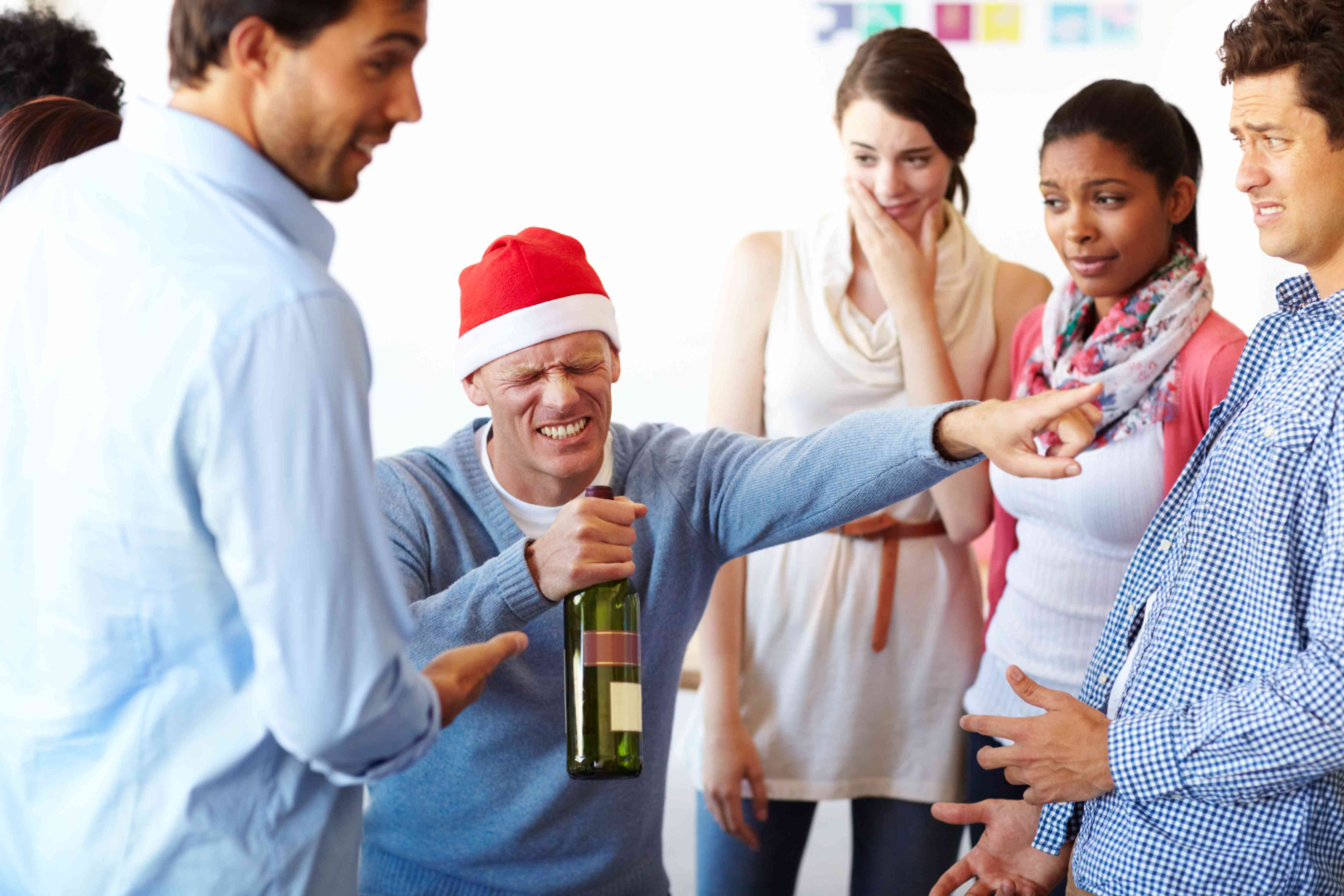 Drunk man with a wine bottle at a staff holiday party