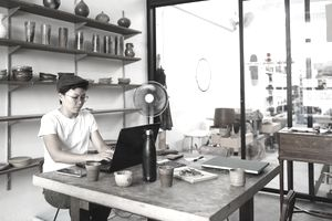 Person works on laptop in pottery store and workshop