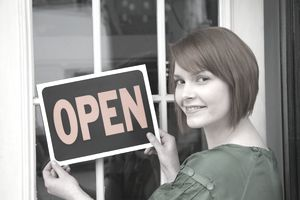 "Woman hanging an ""open"" sign on the door of her business."