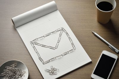 An envelope outline, made of paperclips next to a cellphone, symbolizing email