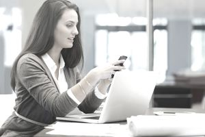 Businesswoman using smart phone in office