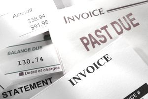 Past due bills and an invoice piled on top of each other