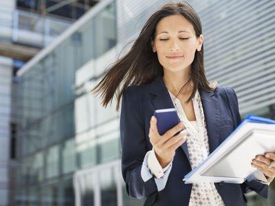 Businesswoman using cell phone outside office