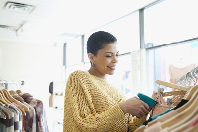 Store owner adding pricetags to clothes
