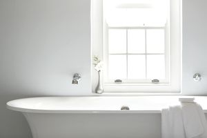 Soaking tub below window in luxury bathroom