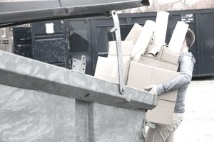 Man carrying cardboard to the recycling bin.