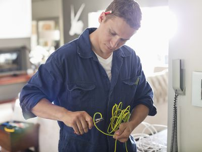 Electrician cutting wires in home