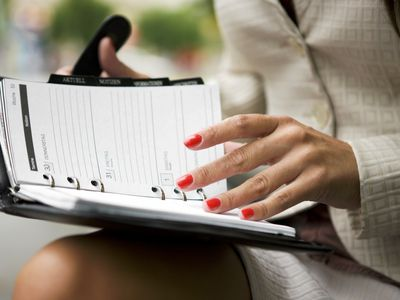 woman looking at business calendar open in her lap representing the concept of time management.